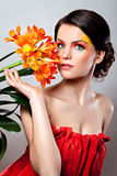 Beautiful girl with an orange flower Stock Photos