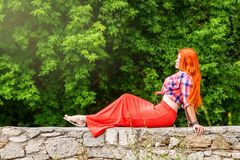 Beautiful girl with orange hair in plaid shirt and red - pink sk Royalty Free Stock Photo