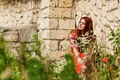 Beautiful girl with orange hair in plaid shirt and red - pink sk Royalty Free Stock Photography