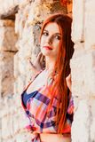Beautiful girl with orange hair in plaid shirt and red - pink sk Royalty Free Stock Image
