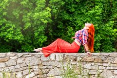 Beautiful girl with orange hair in plaid shirt and red - pink sk Royalty Free Stock Photos
