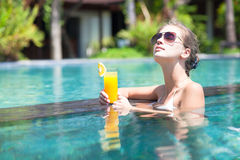 Beautiful girl with orange juice in luxury pool. Beautiful girl with fresh orange juice in luxury pool royalty free stock photography