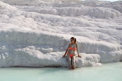 Beautiful girl in orange swimsuit stands near white stone at Pamukkale. Province of Denizli in the south-west of Turkey. Stock Images