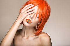 Beautiful girl in an orange wig cosplay style with bright creative lips. Art beauty image. Royalty Free Stock Image