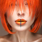 Beautiful girl in an orange wig cosplay style with bright creative lips. Art beauty image. Portrait shot in the studio Royalty Free Stock Images