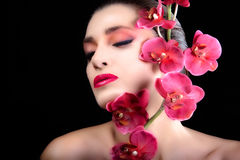 Beauty face. Beautiful Girl With Orchid Flowers. Pink Makeup. Beauty face of the young beautiful woman with orchid flowers Stock Image