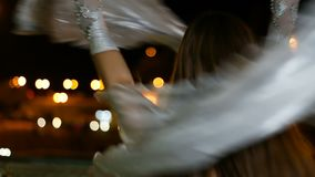 Beautiful girl in oriental costume is dancing fan dance at night outdoor stock video footage