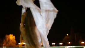 Beautiful girl in oriental costume is dancing fan dance at night outdoor stock video