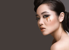 Beautiful girl with oriental type evening hair and makeup with a drop on her face. Beauty face. Royalty Free Stock Image