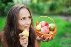 Beautiful girl outdoor with apples and pears in th. E crib Stock Image
