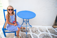 Beautiful girl in outdoor cafe on street of typical greek village on Mykonos Island, Greece Stock Photos