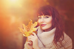 Beautiful girl outdoors with autumn leaves Stock Image