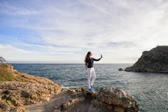 Beautiful girl outdoors. Spring day. The girl with long hair photographes itself near the sea stock photo