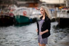 Beautiful girl outdoors. Spring day. The girl near boats on a marina royalty free stock image