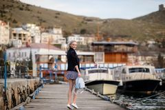 Beautiful girl outdoors. Spring day. The girl near boats on a marina royalty free stock images