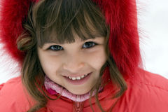 Beautiful girl outdoors in winter. Beautiful european girl Victoria  in red jacket are laughing outdoors in winter Stock Image