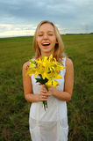 Beautiful girl outside breathing fresh air. A beautiful girl standing in a field holding fresh flowers breathing in fresh air Stock Images