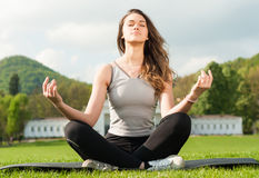 Beautiful girl outside in summer park sitting in lotus pose Royalty Free Stock Photos