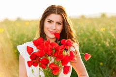 Beautiful Girl over Sky and Sunset in the field holding a poppies bouquet and smiling Royalty Free Stock Photo