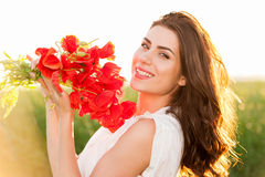 Beautiful Girl over Sky and Sunset in the field holding a poppies bouquet, smiling Royalty Free Stock Photography