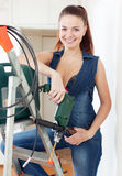 Beautiful  girl in overalls with drill Royalty Free Stock Images