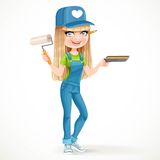Beautiful girl in overalls holding a roller and tray with paint Royalty Free Stock Photography