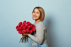 Beautiful girl in the overalls with red roses in hands on a blue background. Women`s hands are holding a bouquet of. Beautiful girl in the overalls with red Stock Image