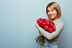 Beautiful girl in the overalls with red roses in hands on a blue background. Women`s hands are holding a bouquet of. Beautiful girl in the overalls with red Royalty Free Stock Photos