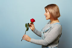 Beautiful girl in the overalls with red roses in hands on a blue background. Women`s hands are holding a bouquet of roses. Beautiful girl in the overalls with Royalty Free Stock Photography