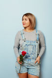 Beautiful girl in the overalls with red roses in hands on a blue background. Women`s hands are holding a bouquet of roses. Beautiful girl in the overalls with Stock Photo