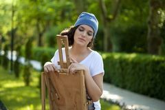 Beautiful girl painter posing for a photo shoot. A girl with an easel royalty free stock image