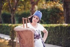 Beautiful girl painter posing for a photo shoot. A girl with an easel royalty free stock photography