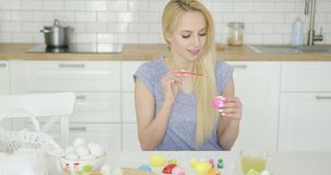 Beautiful girl painting on Easter eggs stock video footage