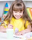 Child painting Easter eggs. Beautiful girl painting eggs at home. Happy child preparing for Easter Royalty Free Stock Photos