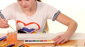 Beautiful girl paints color a stripes paper on stock footage