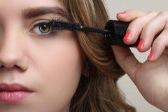 Beautiful girl paints eyelashes Stock Images