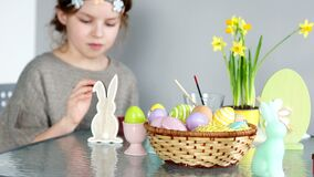 The beautiful girl paints the figure of the Easter bunny. There are paints on the table, a basket with Easter eggs and a. Bouquet of daffodils stock footage
