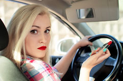 Beautiful girl paints her lips while driving a car Royalty Free Stock Photos