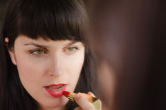 Beautiful girl paints her lips red Stock Image