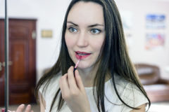 Beautiful girl paints lips in the office Royalty Free Stock Images