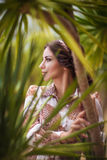 Beautiful girl in palm leaves Stock Photos