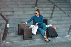 Beautiful girl with paper bags sits on a stairs outside shopping mall. Young beautiful girl in a jeance in sunglasses with paper bags sits out of shopping mall royalty free stock photo