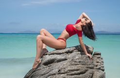 Beautiful girl on paradise beach. Beautiful brunette woman in red bikini and sunglasses posing on the rock of sandy paradise island beach over blue sea and sky Royalty Free Stock Image