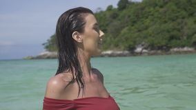 Beautiful girl on paradise beach. Closeup face of beautiful brunette woman in red bikini smiling and walking in the sea water of paradise island beach - video in stock video