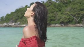 Beautiful girl on paradise beach. Beautiful woman in red bikini playing with her hair while walking in the sea water of paradise island beach - video in slow stock video footage