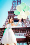 Beautiful girl in Paris with Eiffel tower on background. Girl in a romantic dress with balloons in hands Stock Photo