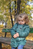 Beautiful girl in the park. Beautiful little girl sitting on a  bench in an autumn park Stock Images