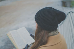 Beautiful girl on a Park bench reading a book Royalty Free Stock Images