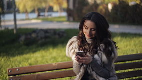 Beautiful girl in the park on a bench writing sms phone stock video
