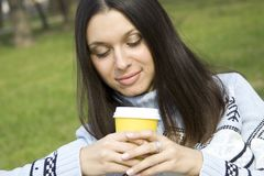 Beautiful girl in a park drinking coffee Royalty Free Stock Photo